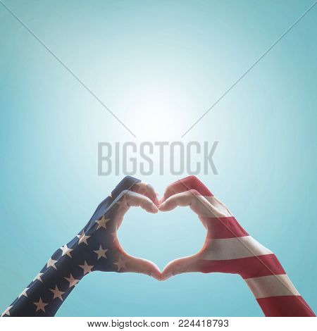 American Flag Pattern On People Hands In Heart Shaped Form Against Vintage Sky Background W/ Clouds: