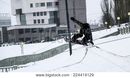 snowboarding. jump on snowboard. freestyle. jump from a springboard on a snowboard in the city. Grab. free ride