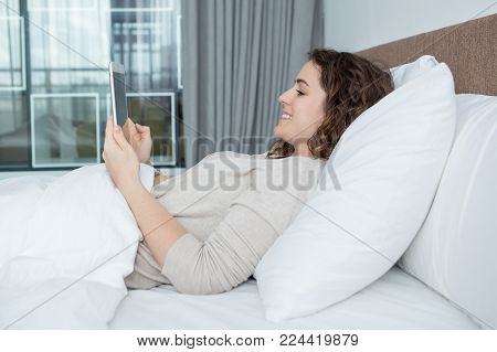 Smiling Caucasian woman lying in bed and looking at tablet screen. Young woman having video chat during bed rest. Bed rest and communication concept
