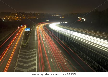 Long exposure of light trails on the M3 motorway as it sweeps through the coutryside with the lights of Winchester twinkling in the distance. poster