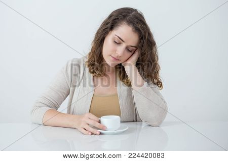Upset Caucasian woman sitting at table with cup of tea, leaning head on hand and looking down. Pensive young lady thinking over unexpected troubles. Tea break or bad news concept