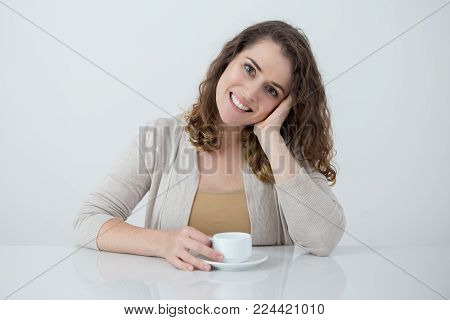 Happy Caucasian woman sitting at table, holding cup of coffee and smiling at camera. Attractive business woman on meeting with partners. Tea or coffee break or communication concept