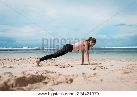 Fitness woman planking doing yoga exercises. Girl training her abs exercising core muscles with the plank pose.