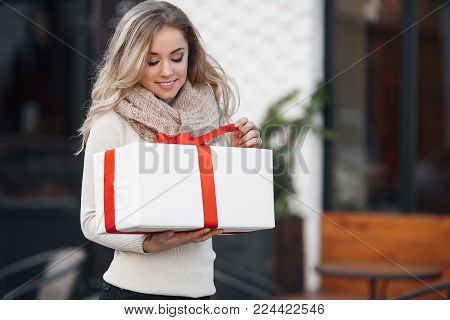 Pretty girl with long blonde hair,standing alone in the open air,holding a Christmas gift. Christmas woman with gift box.Cute young blonde in a white winter sweater with a red gift box, Christmas, New year, Valentine's Day gift