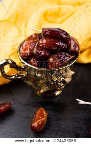 Dry fruit dates in golden cup near slate black heart. Copy space