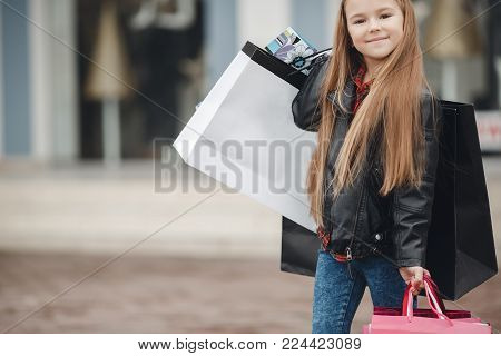 Stylish Little Girl With A Bunch Of Bags For Shopping At The Supermarket.smiling Little Girl With Sh