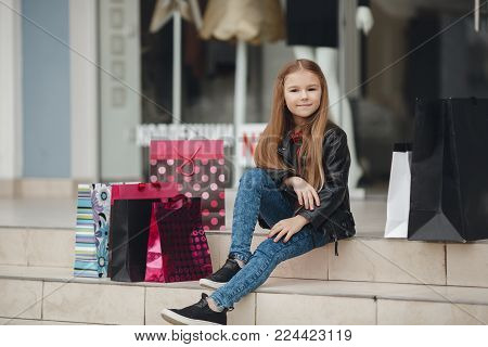 Stylish little girl with a bunch of bags for shopping at the supermarket.Smiling little girl with shopping bags with gifts. Happy child holds a lot of shopping bags with gifts. Black Friday sale holidays concept. Kids shopping