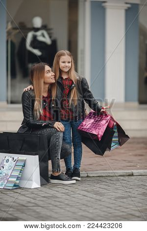 Beautiful Mom And Her Cute Little Daughter Are Holding Shopping Bags Looking At Camera And Smiling W