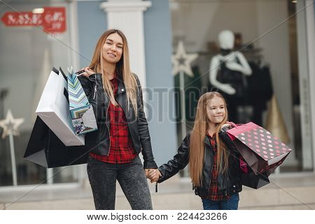 Beautiful mom and her cute little daughter are holding shopping bags looking at camera and smiling while standing together in the open air.Mother and daughter walking in mall smiling.Young mother and her daughter doing shopping together