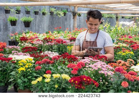 Worker Using Digital Tablet In Flower Shop