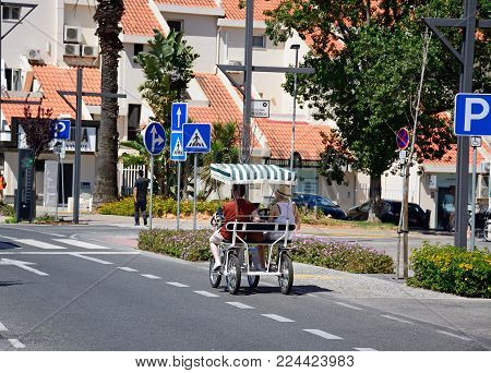 VILAMOURA, PORTUGAL - JUNE 6, 2017 -Couple riding in a two seater pedal car in the town, Vilamoura, Algarve, Portugal, Europe, June 6, 2017.