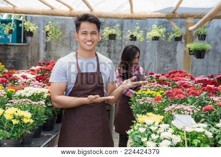two happy asian male and female florist in the flower shop
