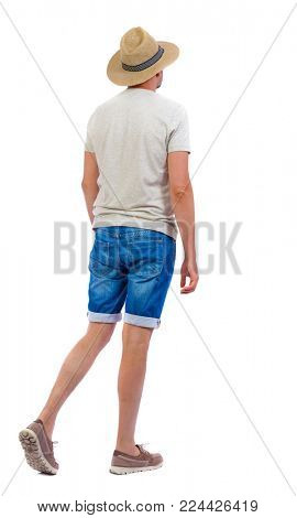 Back view of going  handsome man. walking young guy . Rear view people collection.  backside view of person.  Isolated over white background. a guy in denim shorts and a hat goes forward.