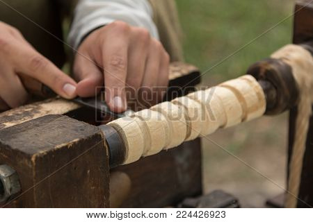 Carver at Work with Cutting Equipment during Medieval Country Festival.