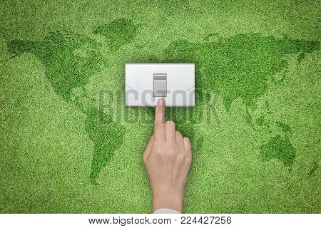 Energy Saving And Ecological Friendly Concept With Hand Turning Off Switch On Green Grass Lawn With