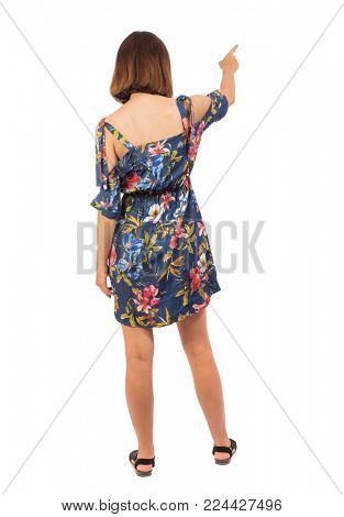 Back view of  pointing woman. beautiful girl. Rear view people collection.  backside view of person.  Isolated over white background.  The girl in a colorful dress shows a finger in the side