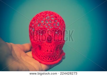 Skull printed with plastic of red color on a 3d printer. Skull printed on 3d printer in man's hand. Progressive modern additive technology