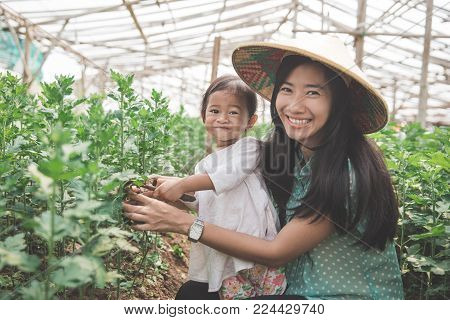 Child and his mother doing some farming together in the greenhouse