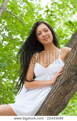 Portrait Of A Young Girl Sitting In A Tree
