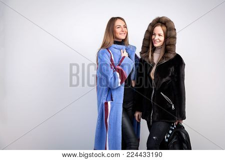 Two young beautiful women in black and naked fur coats from natural fur mink talking and posing on white isolated background