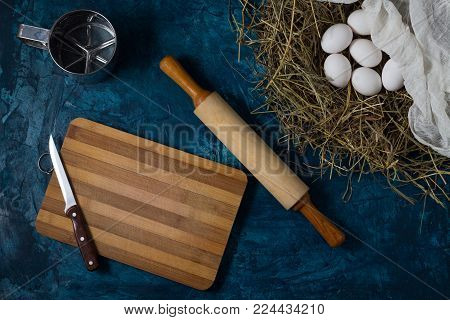 Eggs in the Nest, kitchen accessories, knife, rolling pin, cutting board on the Blue Background. Copy space. Flat lay, top view.