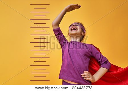 Little child is playing superhero. Kid is measuring the growth on the background of bright color wall. Girl power concept. Yellow, red and violet colors.