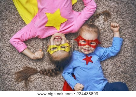 Little children are playing superhero. Kids on the floor, top view. Girl power concept.