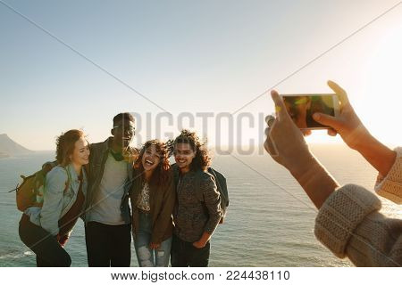 Couple Sitting On The Top Of Mountain And Taking Selfie