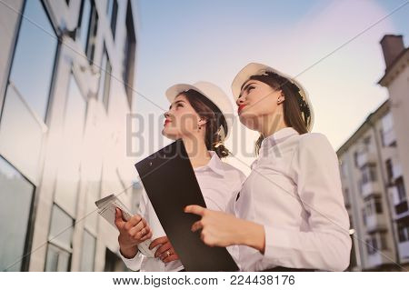 Two young pretty business women industrial engineers in construction helmets with a tablet in hands on a glass building background. Construction plan, architect, designer, successful