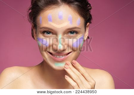 Happy girl doing makeup using concealer. Photo of beautiful brunette girl on pink background. Skin care concept
