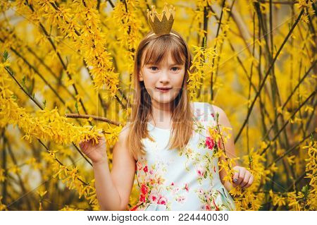 Young little 9-10 year old girl, wearing beautiful dress and gold crown headband, blowing a kiss