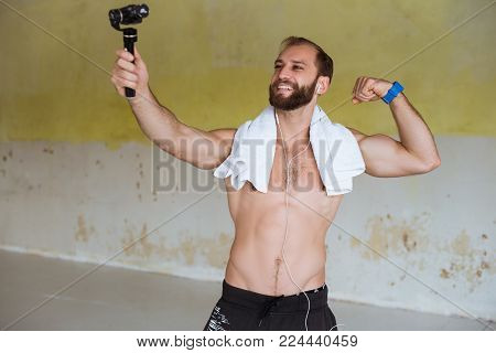 Image of happy young sportsman staying in gym and make selfie on action camera with stabilizer .