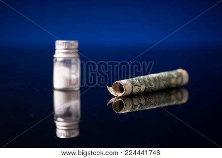cocaine or other illegal drugs that are sniffed by means of a tube, isolated on black glossy background