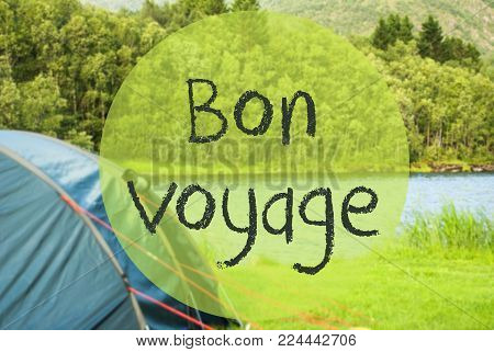 French Text Bon Voyage Means Good Trip. Camping Holiday In Norway At Lake Or River. Green Grass And Forest In Background. Tent In The Front