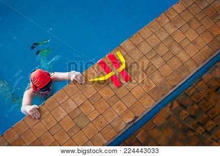 Boy swimmer, participant in underwater struggle - aquatlon, clings to the side of the pool after the end of his combat.