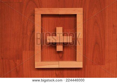 Wooden blocks in shape of Cross in frame on wooden background