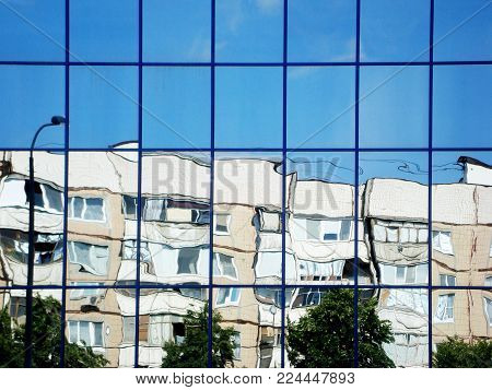 City reflection in mirrored walls of shopping mall. Blue sky reflected in mirror windows of house. Modern mirrored building downtown.