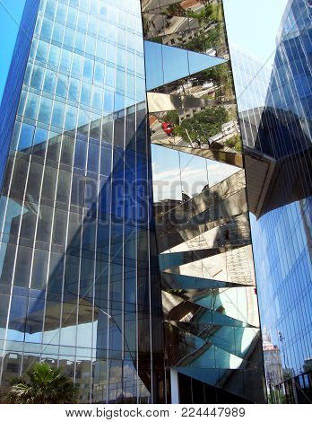 City reflection in mirrored walls of build. Blue sky reflected in mirror windows of house. Modern building downtown.
