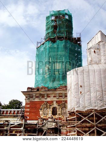 Restoration work on recovery of orthodox or catholic church. Facade of old temple in scaffolding. Chapel on sky background.