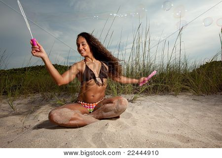 Young Brunette Woman At The Beach Playing With Bubbles Enjoying Herself