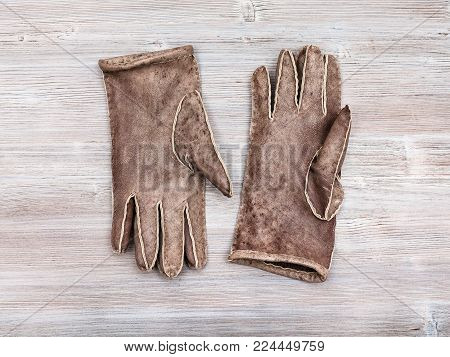 workshop on sewing gloves - top view of new hand-made sewn gloves on wooden background