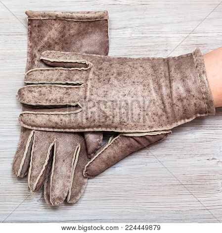 workshop on sewing gloves - top view of hand in new hand-made glove on wooden background