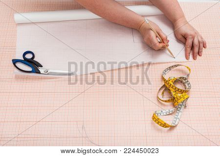tailor copies the hand drawn clothing pattern on tracing paper