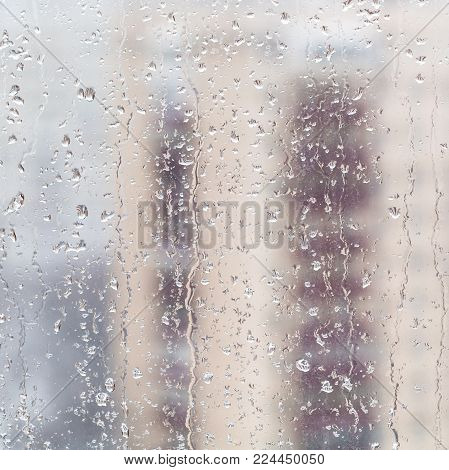 urban background - melting snow on home window glass (focus on water trickles on windowpane) in winter season