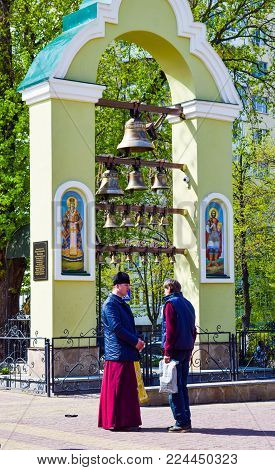 Kiev, Ukraine - April 16, 2017: The priest converses with a parishioner near a small bell tower.