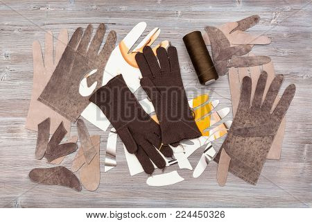 workshop on sewing gloves - top view of various details for gloves production on wooden background