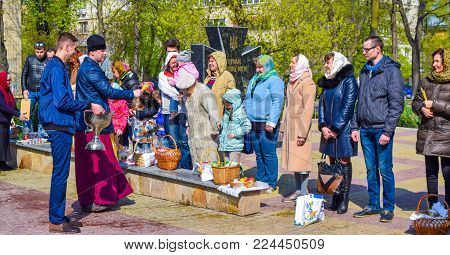 Kiev, Ukraine - April 16, 2017: The priest during Easter consecration of eating and parishioners holy water.