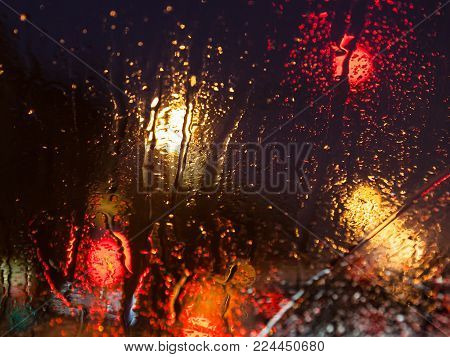 driving in night snowfall in Moscow - trickle of water from melting snow on car windshield in winter evening (focus on car window glass though wet windscreen)