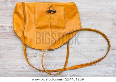 top view of handmade yellow leather bag on wooden table