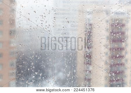 urban background - drops of melting snow on window glass (focus on water trickles on windowpane) in winter season